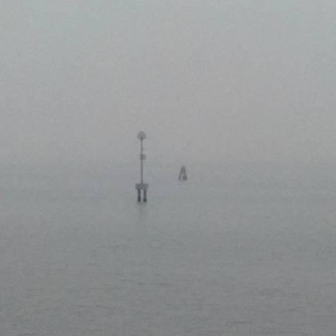Venezia - Bricola in the mist. A black and white coloured photo.